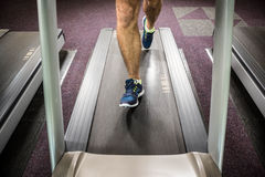 Lower section of man running on treadmill Royalty Free Stock Photography
