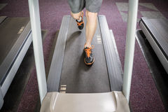Lower section of man running on treadmill Stock Photos