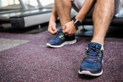 Lower section of man sitting on treadmill and tying the shoelace Royalty Free Stock Images