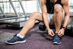 Lower section of man sitting on treadmill and tying the shoelace Stock Images