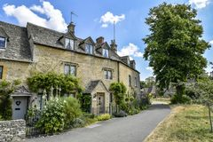 LOWER SLAUGHTER, THE COTSWOLDS, GLOUCESTERSHIRE, ENGLAND Cotswold stone cottages in summer afternoon sunlight royalty free stock photos