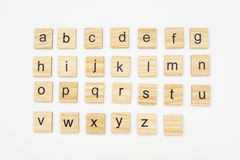 Lowercase alphabet letters on scrabble wooden blocks. Isolated on white background royalty free stock photography