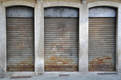 Lowered rolling shutters. Of a disused shop, rusty, dirty and failure cityscape Stock Images