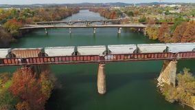 Lowering aerial view of train on Bridge in Austin Texas. Austin, TX - Circa December, 2017 - A lowering aerial view of a train traveling on a bridge over the stock video