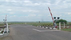 Lowering the barrier at the railway crossing. Lowering of the barrier at the railway crossing. Empty road without cars stock footage