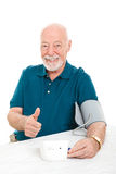 Lowering Blood Pressure Success. Senior man succeeds in lowering his blood pressure and gives a thumbs up sign.  White background Stock Photo