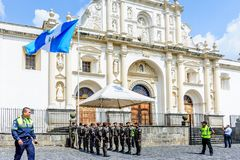 Lowering of Guatemalan flag on Independence Day, Guatemala. Antigua, Guatemala - September 15, 2017: Soldiers lower Guatemalan flag alongside Mayor of Antigua Stock Photography
