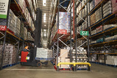 Lowering stock in a distribution warehouse using aisle truck stock photos