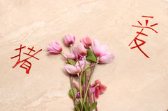 Lowers and chinese symbols. Flowers and chinese symbols in a stone background stock photo
