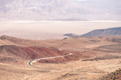 The lowest point in America, Death Valley Arizona. This picture shows the desert of Death Valley with a winding road cut through the mountains leading down to royalty free stock photos