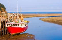 Lowest Tide Worldwide. Red moored boat sitting on the bottom of the Atlantic Ocean during low tide Stock Photography
