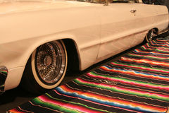 Lowrider car. An awesome cream-colored classic lowrider car on display with a Mexican serape on the ground beside it Royalty Free Stock Photography