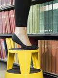 Lowsection der Frau auf dem Schemel, der für Buch erreicht Stockbilder