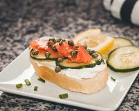 Lox and Cream Cheese with Capers, a Slice Cucumber and a Squeeze. Finger sandwich with smoked salmon and cream cheese.  Capers and sliced cucumber are included Stock Image