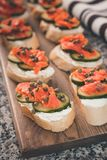 Lox and Cream Cheese with Capers, a Slice Cucumber and a Squeeze. Several finger sandwiches with smoked salmon and cream cheese cover a cutting board.  Capers Royalty Free Stock Photo