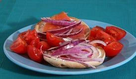 Lox och baglar med lökar och tomater Arkivfoton