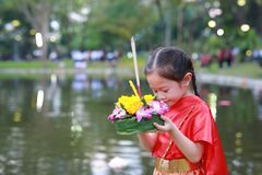 Loy Krathong festival, Asian Child girl in Thai traditional dress with holding krathong for forgiveness Goddess Ganges to celebrat stock image