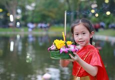 Loy Krathong festival, Asian Child girl in Thai traditional dress with holding krathong for forgiveness Goddess Ganges to celebrat royalty free stock photography