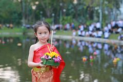 Loy Krathong festival, Asian Child girl in Thai traditional dress with holding krathong for forgiveness Goddess Ganges to. Celebrate festival in Thailand stock photo