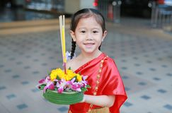 Loy Krathong festival, Asian Child girl in Thai traditional dress with holding krathong for forgiveness Goddess Ganges to. Celebrate festival in Thailand stock image
