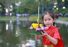 Loy Krathong-Festival, asiatisches Kindermädchen im thailändischen Trachtenkleid mit Holding krathong für Verzeihen Göttin der Ga lizenzfreie stockfotografie