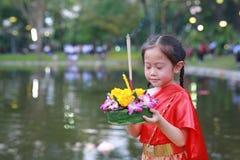 Loy Krathong festival, asiatisk barnflicka i thailändsk traditionell klänning med innehavkrathong för förlåtelsegudinnan Ganges t arkivfoton