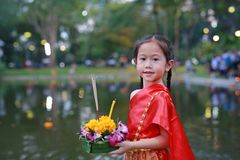 Loy Krathong-festival, Aziatisch Kindmeisje in Thaise traditionele kleding met holding krathong voor vergiffenisgodin Ganges aan stock foto