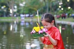 Loy Krathong festiwal, Azjatycka dziecko dziewczyna w Tajlandzkiej tradycyjnej sukni z mienia krathong dla przebaczenie bogini Ga obraz stock