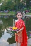 Loy Krathong festiwal, Azjatycka dziecko dziewczyna w Tajlandzkiej tradycyjnej sukni z mienia krathong dla przebaczenie bogini Ga zdjęcia stock