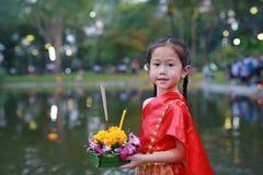 Loy Krathong festiwal, Azjatycka dziecko dziewczyna w Tajlandzkiej tradycyjnej sukni z mienia krathong dla przebaczenie bogini Ga zdjęcie stock