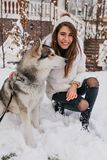 Loyal dog looking away in winter day while laughing girl in white jacket stroking him. Spectacular european lady in stock photos