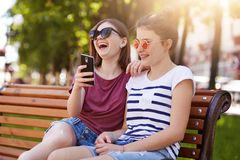 Loyal happy friends feel good near each other in the park. Beautiful cheerful girls read funny unpredictable story on bench burst stock photos