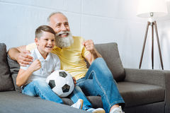 Grandfather and grandson rooting for their favorite football team Royalty Free Stock Image