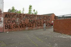 Loyale Warnung auf einer Backsteinmauer, Belfast. lizenzfreie stockbilder