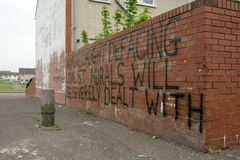 Loyalist warning message on a brick wall, Belfast. Royalty Free Stock Photo