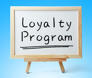 Loyalty Program. Whiteboard with text Loyalty Program is on the blue background Royalty Free Stock Photos