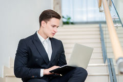 Loyalty to work. Confident businessman sitting on the stairs and Royalty Free Stock Photo
