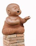 Loza de barro del monje del niño aislada en el fondo blanco Foto de archivo