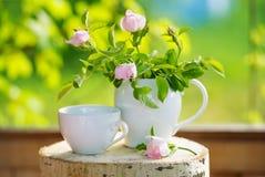 Loza del té y flores color de rosa salvajes imagenes de archivo