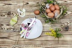 Loza, huevos en la jerarquía y ramas de la mimosa foto de archivo