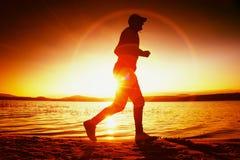 Löpare i solstrålar på stranden Idrottsman i baseballmössan som joggar under soluppgången ovanför havet Arkivfoton