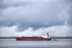 LPG Liquefied Petroleum Gas Tanker Ship Sailing. LPG liquefied petroleum gas tanker bulk carrier ship sailing on a river with a guiding tugboat out of port Stock Photography