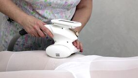 Apparatus for vacuum roller massage LPG. The LPG massage session in the beauty salon is conducted by a girl in a white, hot suit stock video footage