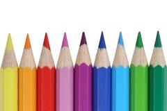 Lápices coloreados de las fuentes de escuela en fila, aislado Foto de archivo libre de regalías