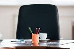 Lápices coloreados en un tarro en el fondo del cha del director Imagen de archivo libre de regalías