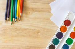 Lápices coloreados, mintiendo como el arco iris, el documento y la acuarela sobre fondo de madera Imágenes de archivo libres de regalías
