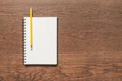 Lápis amarelo com o livro de nota vazio no fundo de madeira Fotos de Stock Royalty Free