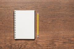 Lápis amarelo com o livro de nota vazio no fundo de madeira Fotografia de Stock Royalty Free