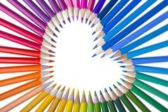 Lápis da cor arranjados em uma forma do coração Fotos de Stock Royalty Free