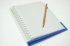 Lápis de madeira posto sobre um caderno Imagem de Stock Royalty Free